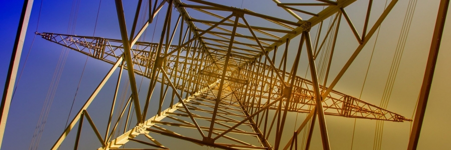A picture of a steel transmission line tower as it would look from underneath when staring at the sky. The background fades from blue to yellow, top left to bottpm right.