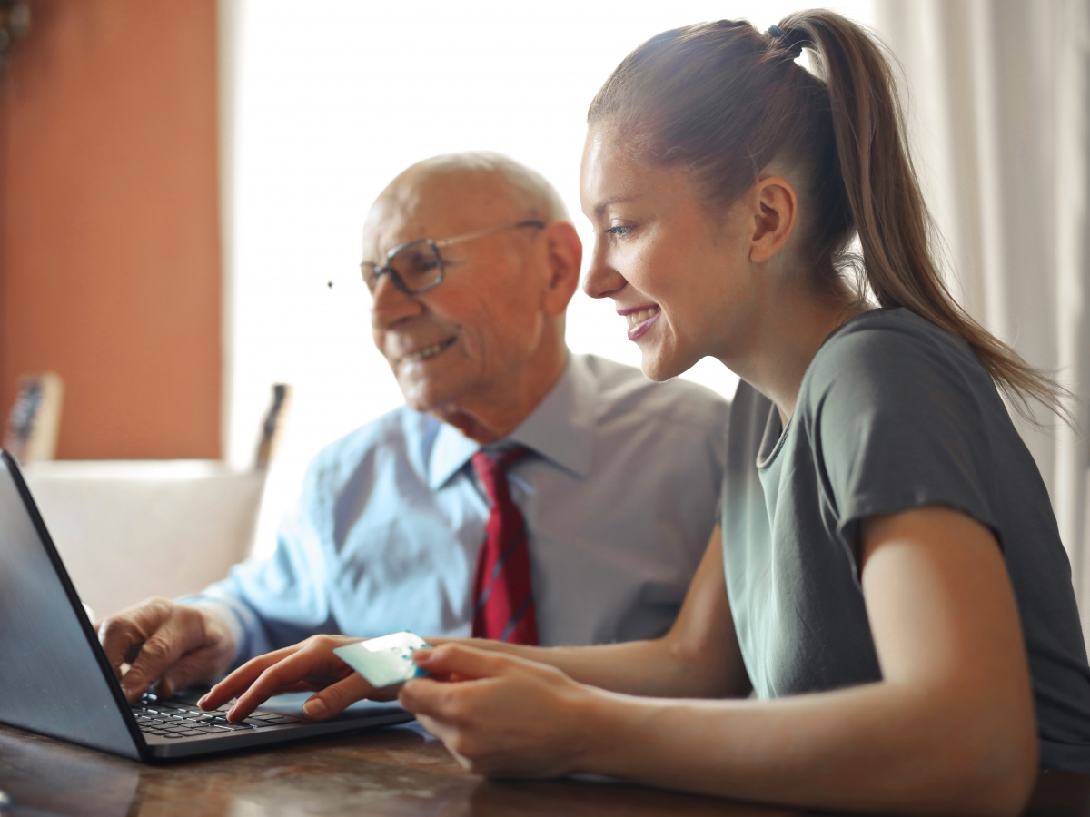 a young woman is assisting an elderly gentleman to make a payment on a laptop