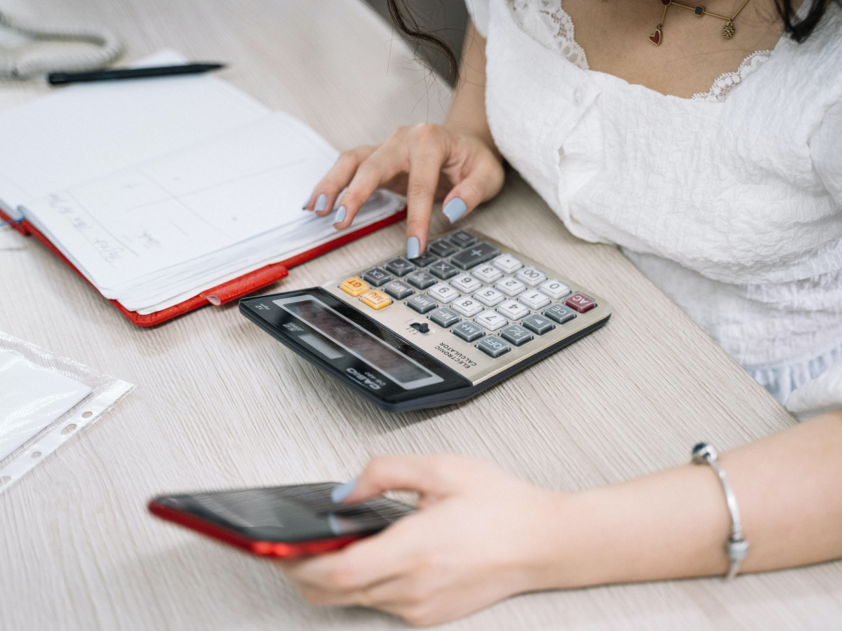 a woman holding a red iphone, typing on a calculatore with a red notebook laying on the desk to her right.