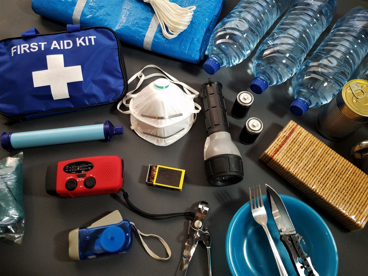 emergency preparedness items such as bottled water, a first aid kit, a flashlight and canned goods are displayed on a gray background.