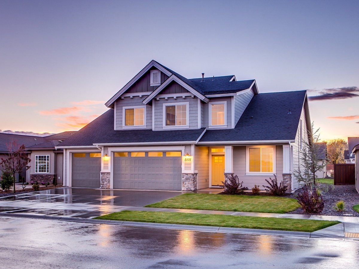 A gray house with black shingles is pictured with lights. The pavement looks wet as if it has just rained.