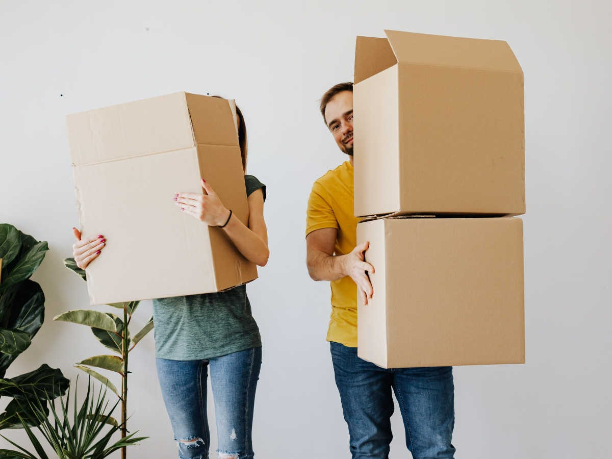 two peope in blue jeans are holding cardboard boxes and standing in fromt of a white wall with some plants on the left.